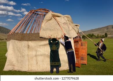 Men in traditional dress assembling wool felt covers over Yurt frame in Saty, Kazakhstan - September 7, 2016