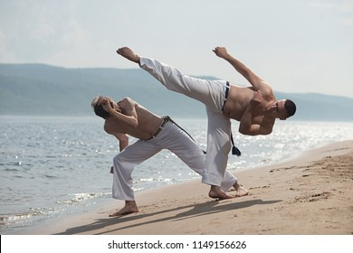 Men train capoeira on the beach - concept about people, lifestyle and sport. Training of two fighters