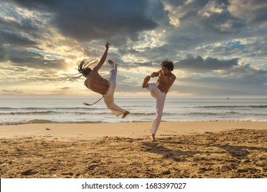 Men train capoeira on the beach - Training of two fighters