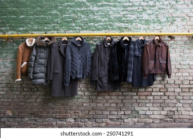 Men trendy clothing on hangers on grunge brick wall. Concept background