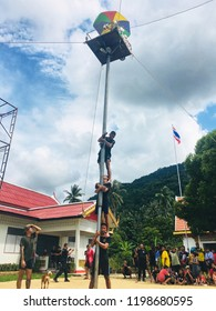 Men trying to climb up to the top of the pole in Traditional game in Festival of Tenth Month. Cheang Khao Temple, Bachao District, Narathiwat Province, Southern, Thailand. October 10, 2018