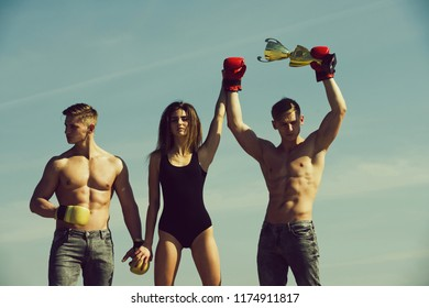 men twins of boxer winner and looser in boxing glove hold champion cup with coach girl outdoor on blue sky. Sport