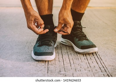 Men are tying up their feet. Before going to jogging,Men are binding shoes