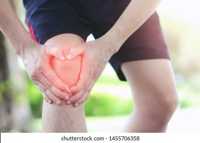 Men use their hands to hold their knees while running on the streets of the park. Copy area for text or design