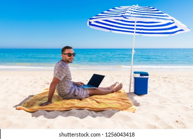 Men using a laptop computer on the beach. Freelance Concepts