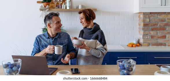 Men using laptop and driking coffee at home and talking with his wife