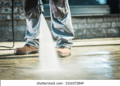 Men Using Pressure Washer For Driveway Cleaning.