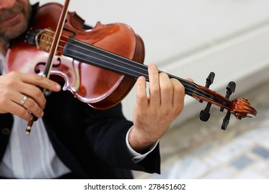 Men Violinist Playing Classical Violin Music in Musical Performance