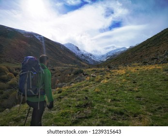 Men walking alone in a green field with mountains around