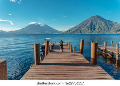 Men walking along jetty at Lake Atitlán looking San Pedro Volcano and Atitlán Volcano, Guatemala