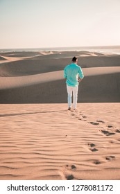 Men walking at the beach of Maspalomas Gran Canaria with sand dunes dry desert of Gran Canary islands. Men walking sand dunes foot steps