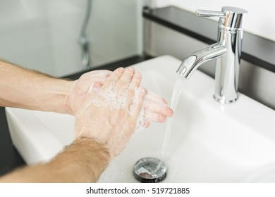 A men washing hand on the sink