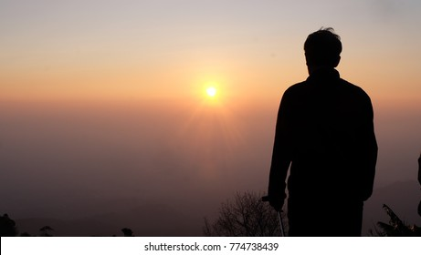 Men  watch the sunrise on Phu tabberk Moutain, Thailand