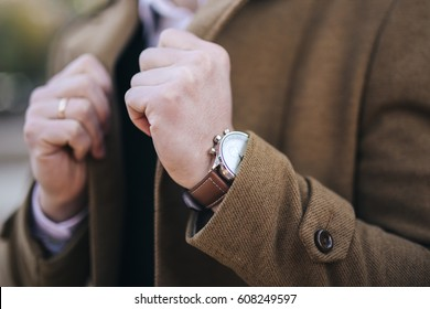Men watches on hand in coat