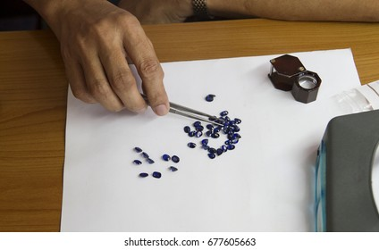 Men are watching the blue sapphire at the gem market
