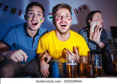 Men watching football match at home while girlfriend is bored