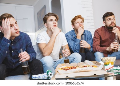 Men watching sport on tv together at home worry