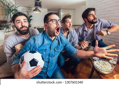 Men watching sport on tv together at home screaming cheerful. Group of friends sitting on the couch and watching a football game.