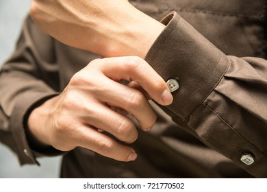 Men wear brown long-sleeved shirts in the dressing room.,Shirt button
