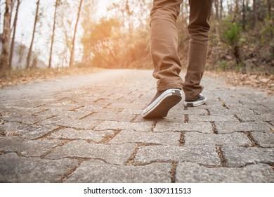 Men wear sneakers and walking on the street.