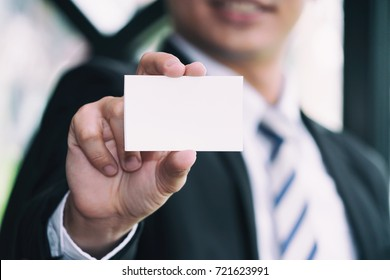 Men wear a suit holding white business card Blurred background, White blank paper In hands of businessman,business concept.