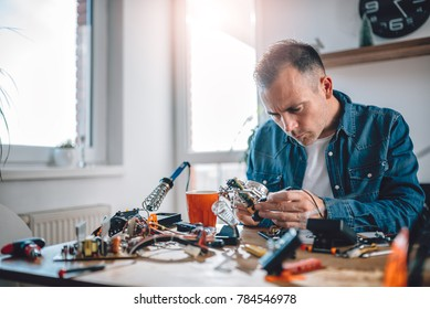 Men wearing blue denim shirt working with electronic components at his home office