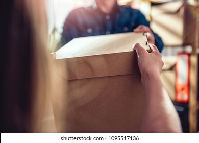 Men wearing blue jean shirt receiving package from courier at the office
