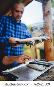 Men wearing blue paid shirt grilling fish on electric barbecue