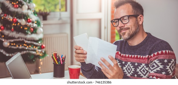 Men wearing blue sweater and eyeglasses opening christmas letter
