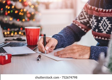 Men wearing blue sweater writing greeting cards at home office during christmas