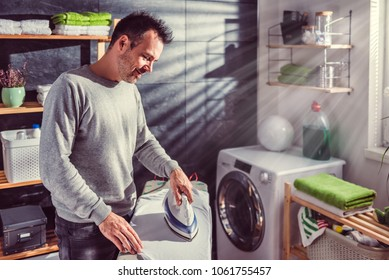 Men wearing grey sweater ironing clothes on ironing board in laundry room at home
