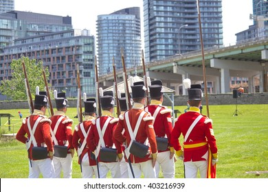 Men wearing historical military uniform march at Fort York in Toronto, Canada.