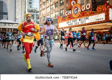 "Men wearing a Hulk Hogan and a ""Macho Man"" Randy Savage costumes pass the Chicago Theatre while competing in The Chicago Marathon in Chicago, Illinois October 8, 2017."