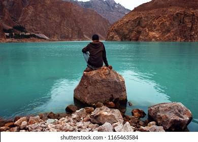 Men Wearing Jacket sitting on rock In Silence And Solitude at Peaceful Attabad Lake, Karakoram Highway, Hunza, Pakistan