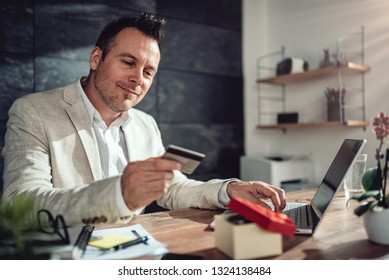 Men wearing linen suit sitting at his desk by the window shopping online and using credit card