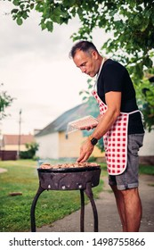 Men wearing red checkered apron barbecuing meat in the backyard