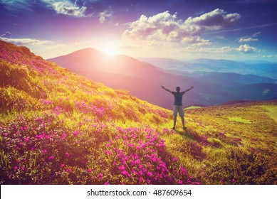 Men welcome sunrise with raised hands in a carpathian mountain valley covered with fresh blossom rhododendrons.