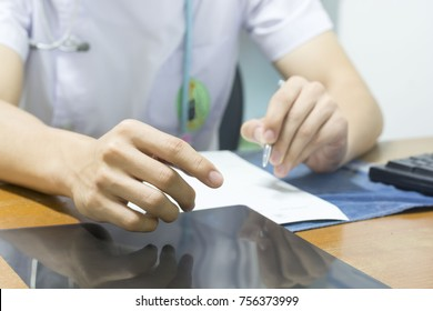 Men were white is reading the results to find the x ray film abnormalities before writing plan to treat patients at the desk in the office room of the hospital.