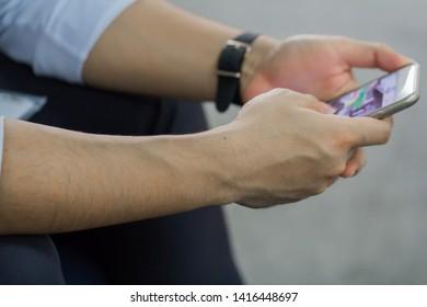Men who are enjoying playing mobile phones.