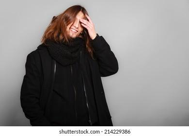 Men winter fashion. Handsome man long hair wearing black coat. Casual look. Studio shot on grey