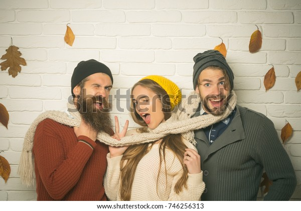 Men and woman, happy family fashion. Girl and men at seasonal brick wall. Friendship, happiness and relations. Season and autumn holiday. Happy friends at autumn leaves in scarf and hat.