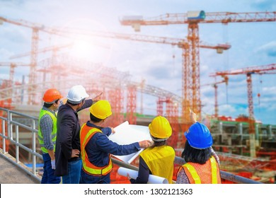 Men and woman meeting with Engineers and supervisors are standing reading the blueprints at the construction site.