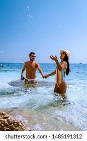 Hombres y mujeres en la playa Cerdeña Italia, jóvenes vacaciones de pareja en Cerdeña Italia, pareja de hombres y mujeres jugando en el océano con agua azul cristalina, hombres y mujeres enamorados en las vacaciones