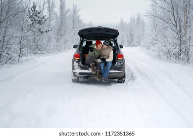 Men and woman wearing casual are having fan in the car in the snow forest, outdoor