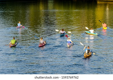 men and women from behind kayaking on a lake