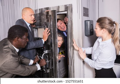 Men and women in business suits solving puzzles to get out of horror style escape room