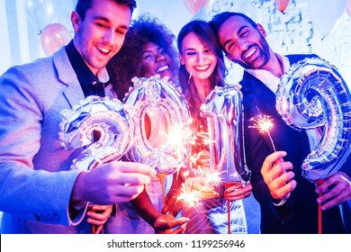 Men and women celebrating the new year 2019 with sparklers and wine