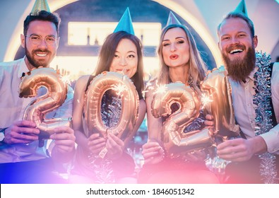 Men and women celebrating the new year 2021 with sparklers and wine