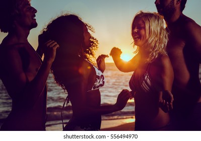 Men and women having party at ocean beach dancing in the sunset