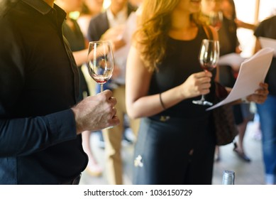 Men and women hold a glass of wine at a celebratory party